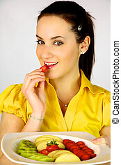 Female model with plate with fruit eating strawberry