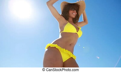 Woman in a yellow bikini dancing
