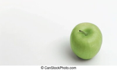 Syringe in super flow motion falling in a top apple against...