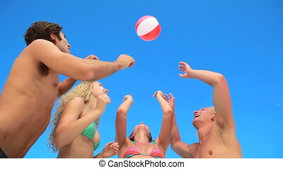 Four friends playing with an inflatable beach ball at the...