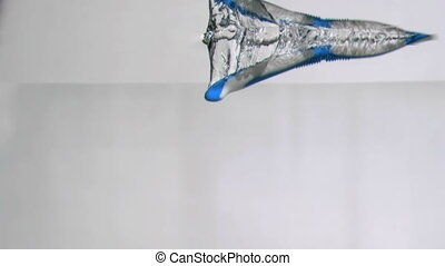 One blue toothbrush in a super slow motion falling in water...