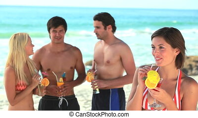 Friends enjoying cocktails at the beach