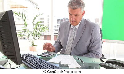Serious businessman calculating bills in an office
