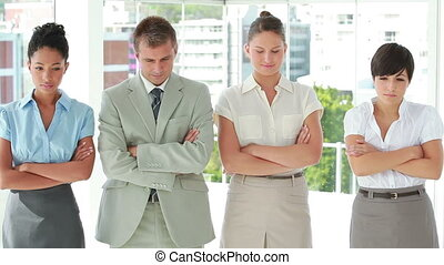 Business people with arms crossed in a line in bright office