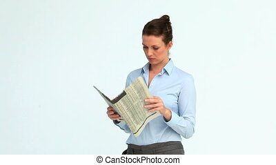 Woman reads a newspaper and crosses her arms against white...