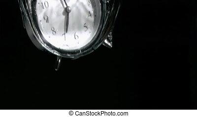 Alarm clock in a super slow motion falling in water against...