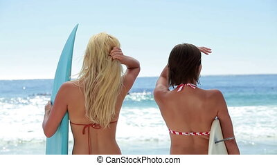 Two surfer women check out the ocean and look for good waves