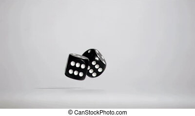 Two black dices in super slow motion rebonding against a...
