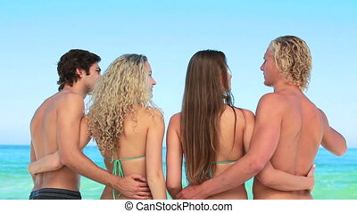Four friends embracing one another at the beach while...