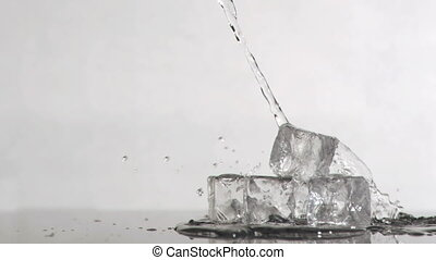 Water falling in super slow motion onto ice cubes against a...