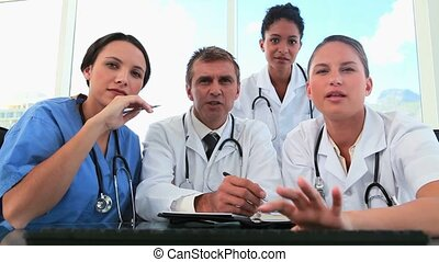 Medical team working together on a computer in a bright...