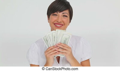 Businesswoman holding a fan of bank notes against a white...