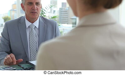 Businessman shaking hands with a woman in an office