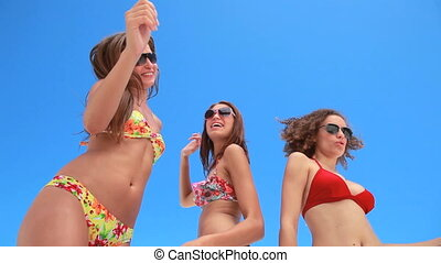 Three girls dancing together in bikinis in front of a blue...
