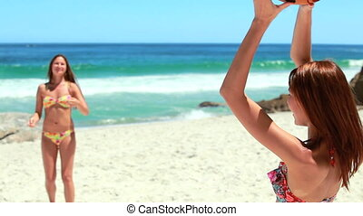 Two girls passing the football to each other at the beach