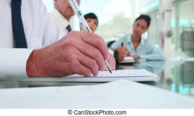 Close-up on a mans hands taking notes with colleagues in a...