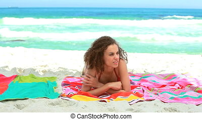 Woman lying on a beach towel is suddenly joined by her...