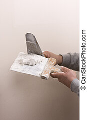Putty Knife with Paste to repair damaged wall