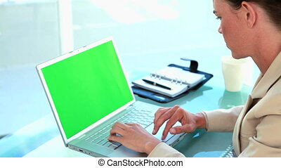 Businesswoman typing on a laptop in a bright room