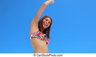 Woman happily dancing in a bikini
