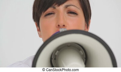 Businesswoman speaking through a megaphone against a white...