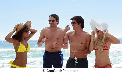 Four friends partying together on the beach