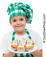 Happy chef boy with a plate of muffins