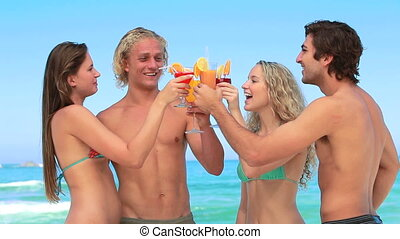 Four friends enjoy cocktails together at the beach