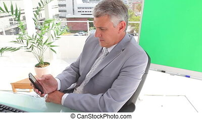 Businessman writing a text message in an office