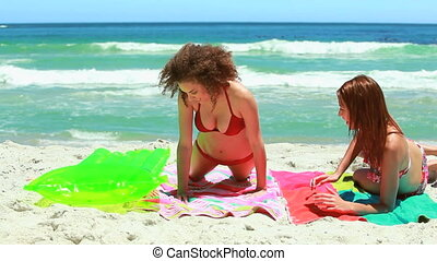 Two girls playing with an inflatable bed in the water