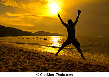 Man jumping on beach sunset - Silhouette happy man jumping...