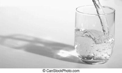 Water flowing in super slow motion into a glass against a...
