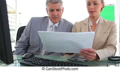 Two colleagues discussing information on a document in an...