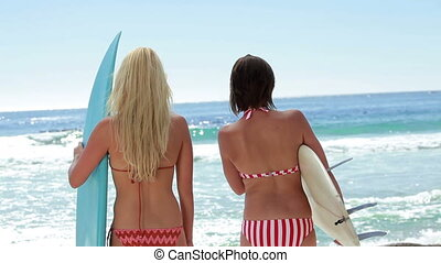 Two female surfers with boards at the beach