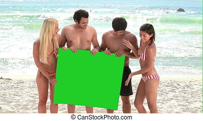 Four people holding onto a green screen in front of the...