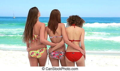 Three women standing together in bikinis
