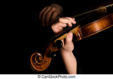 Female hands play a violin on the black