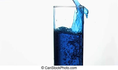 Blue liquid in super slow motion overflowing in a glass