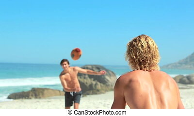 Two guys passing the football to one another while palying...