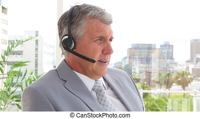 Businessman talking on a headset before smiling in an office