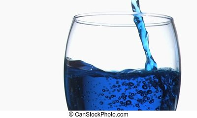 Blue trickle in super slow motion flilling a glass against a...