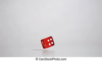 Red dice bouncing in super slow motion against a grey...