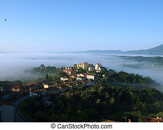 Fabulous landscape of the foggy morning in Tuscany The...