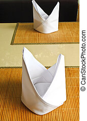 white napkins folded as triangles on the table