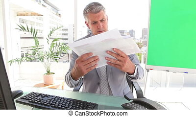 Businessman looking at pages of statistics in an office