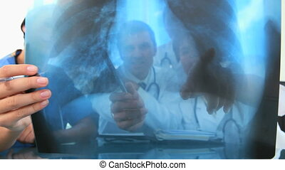 Doctors having a meeting about a chest x-ray in a bright...