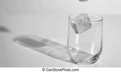 Two ice cubes in a super slow motion rebounding in a glass
