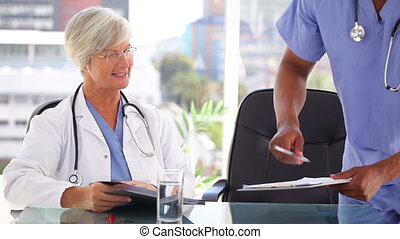 Smiling mature doctor showing documents to a nurse in a...
