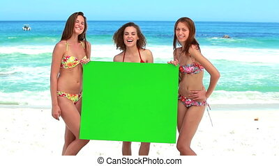 Women holding a blank poster while laughing on the beach