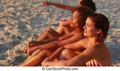 Four friends sit at the beach